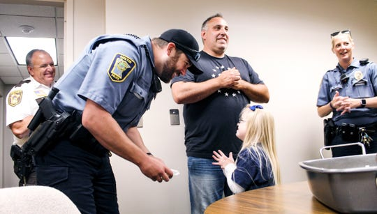 Sophina Lindquist, 10, of St. Cloud, hands an Austin Police Department officer a cookie. Lindquist traveled around Austin on Tuesday, July 30, 2019, delivering cookies to law enforcement, fire fighters and first responders as a way to thank them for their service.
