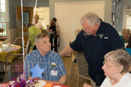 Rotarian Buck Vocelle talks to Florida Baptist Retirement Center resident Burt at the Men's Day Barbecue on Father's Day.