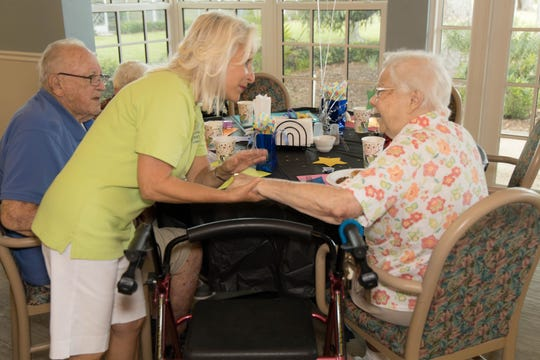 Rotarian Cindy Panijal comforts a resident at the Men's Day Barbecue on Father's Day at the Florida Baptist Retirement Center.