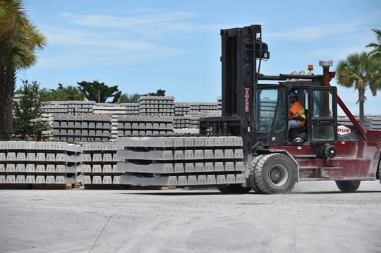A crewman from Rocla Concrete Tie moves completed railroad ties where hundreds are stored at their facility at 600 South 3rd Street on Wednesday, July 31, 2019. in Fort Pierce. Rocla is manufacturing railroad ties for Virgin Trains USA.