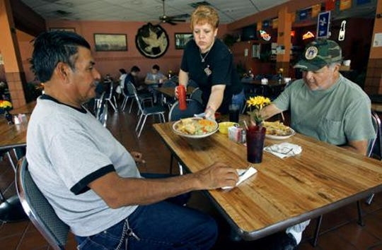 La Paloma server Pat Rodriguez, who as of this Sept. 11, 2006, photo had worked at La Paloma for 21 years, serves lunch to Enrique Robles, left and Felix Ruiz Jr.