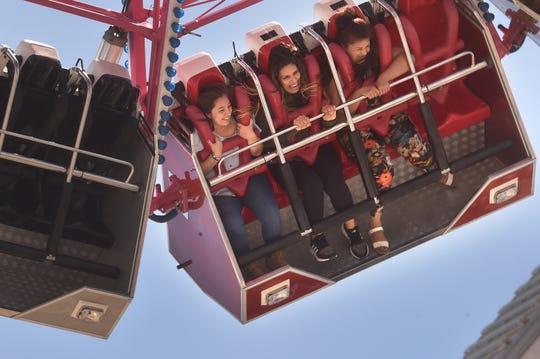 Oxnard residents Mia Espinoza, Vicky Espinoza and Mireya Macias visit the midway on opening day at the Ventura County Fair on Wednesday.