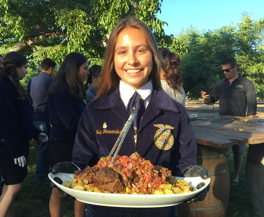 Julia Fernandez, a member of Santa Paula FFA, carries a platter of short ribs, roasted squash and pico de gallo during the From Field to Fork dinner at The Walnut Grove at Tierra Rejada Ranch in Moorpark. The dish was created by the culinary team from Plated Events.