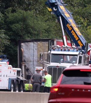 A tow truck crew works on a tractor trailer that had been on fire on the northbound NYS Thruway in Nanuet July 31, 2019. There were heavy traffic delays both northbound and westbound on the Thruway.