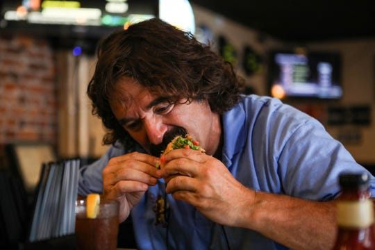 """James Pappas digs in to his meal at James Street Tavern in Newport on Wednesday, July 21, 2019. He's ranked over 300 cheesesteaks based on quality of the roll, meat, """"extras,"""" cheese and overall experience."""