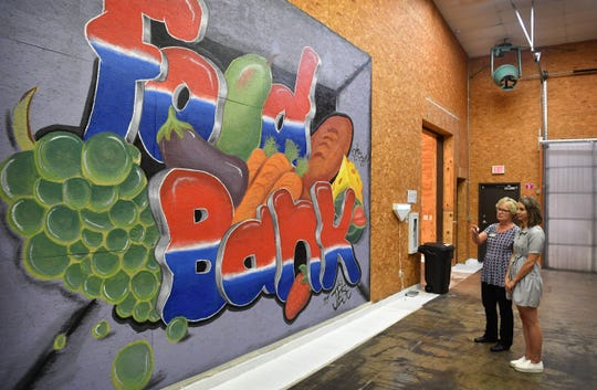 Wichita Falls Area Food Bank Executive Director Kara Nickens, left, and Emily Kincaid, marketing director, look over the new mural painted by artist Jacobie Genus.