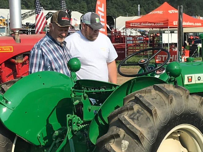 Tractor enthusiasts check out the vintage models at field demonstration at Farm Technology Days in Jefferson County.