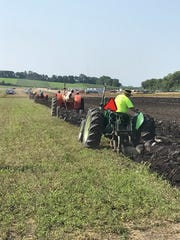 Four tractors pull moldboard plows through a hayfield at Farm Technology Days, paying homage to the event's roots as a plowing contest.