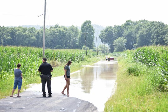 Antritt (right) dips her feet in the water following the incident as Scott Ford walks out to check the car.
