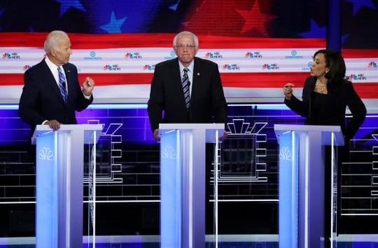 Sen. Kamala Harris (R) (D-CA) and former Vice President Joe Biden (L) speak as Sen. Bernie Sanders (I-VT) looks on during the second night of the first Democratic presidential debate on June 27, 2019 in Miami, Florida.