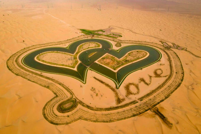 """A picture taken with a drone on July 31, 2019, shows the new man-made """"Love lake"""" at al-Qudra desert in the Gulf emirate of Dubai."""