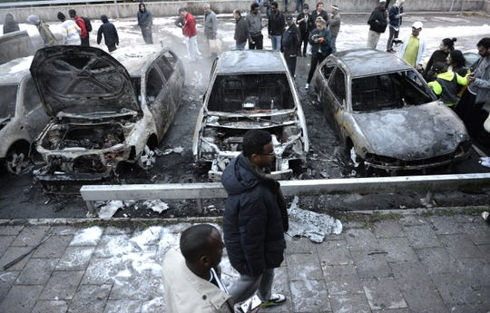 People inspect the scene where cars stand gutted by fire in the Stockholm suburb of Rinkeby after youths rioted in several different suburbs around Stockholm, on May 23, 2013.