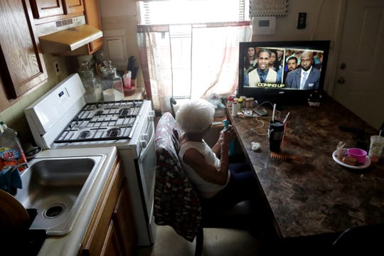 Carrie Newson watches television in the dining area inside her home at the Dutch Village apartments, Tuesday, July 30, 2019, in Baltimore. Newson has complained to management about mice and mold in her home but the issues have yet to be fixed.