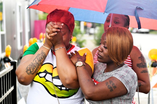 Charvonda Andrews is consoled as she mourns two women killed July 26 while working as volunteers with a group called Mothers Against Senseless Killings, Tuesday, July 30, 2019 in Chicago.