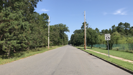 A stretch of Perrineville Road in Jackson where an 1,100-home housing development is planned, to the left. On the right is one of a few quiet neighborhoods.