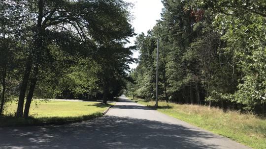 A stretch of Perrineville Road in Jackson where an 1,100-home housing development is planned, to the right. On the left is one of a few quiet neighborhoods.
