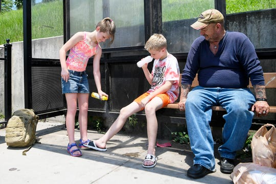 Olyvia Player, 12, sprays her brother, Liam, 11, with sunscreen while they wait for a bus to go to a pool as Eddie Branch looks on with his groceries from nearby Ingles at a stop on Patton Avenue July 19, 2019.