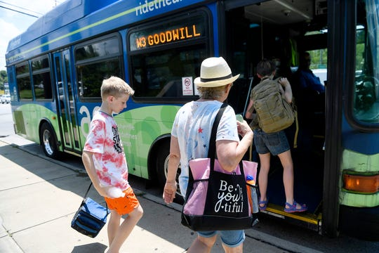 Bea Harwood and her grandchildren, Liam Player, 11, left, and Olyvia, 12, board an Asheville Rides Transit bus on Patton Avenue as they head to a swimming pool in West Asheville July 19, 2019.