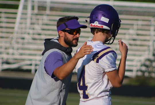 North Kitsap assistant coach Chris Richardson talks to quarterback Skylar Keilbart during the team's 7-on-7 scrimmage in Poulsbo on Wednesday.