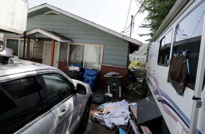 "Vehicles are parked outside the home of Paige A. Thompson, who uses the online handle ""erratic,"" Wednesday, July 31, 2019, in Seattle. Thompson was taken into custody Monday at her home and has been charged with computer fraud and abuse in connection with hacking data from more than 100 million Capital One credit holders or applicants."