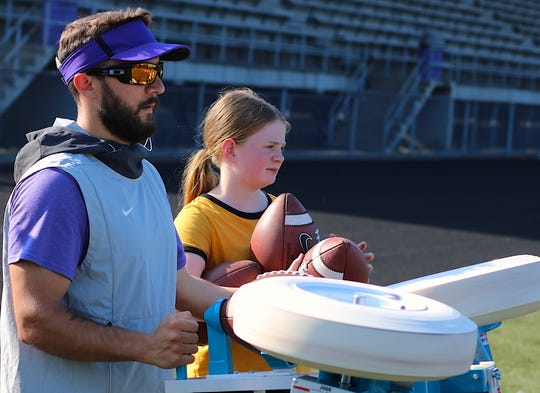 North Kitsap football coach Chris Richardson uses a JUGS passing machine during a 7-on-7 scrimmage in Poulsbo on Wednesday while head coach Jeff Weible's daughter Campbell holds a couple footballs nearby. Richardson is entering his 10th season as an assistant with the Vikings.