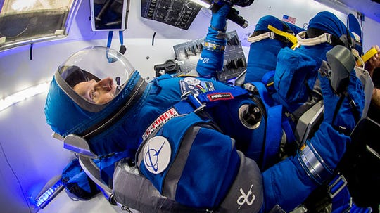 Boeing's Starliner spacesuit features lightweight fabric and an integrated helmet. Here astronaut Chris Ferguson wears the spacesuit inside a mock Starliner capsule.