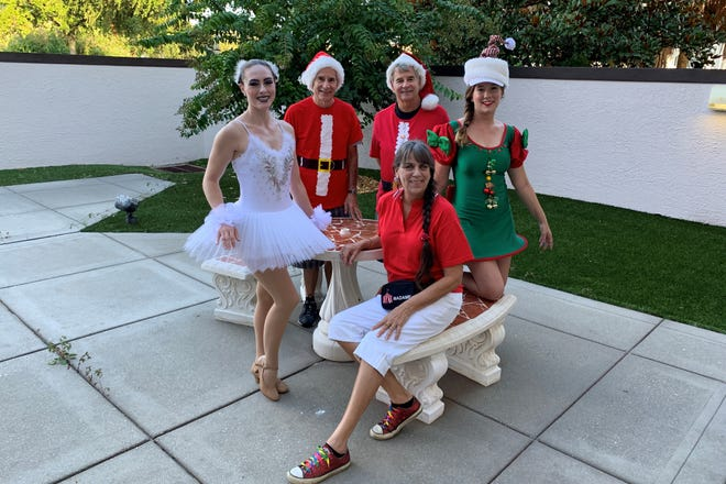 Laurie Allen, seated, is surrounded by performers she supplied for the Christmas in July Sip and Stroll in Cocoa Village. From left are Nicolyn Aleprete, Bob Commons, Steve Commons and Emily Horton.