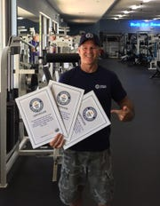 Steve Salmasian of Port St. Lucie holds up the three certificates he's earned for three times breaking the Guinness Book of World Records record for most diamond pushups in one minute