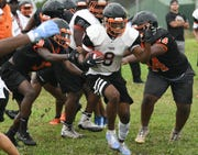 Cocoa High football players prepare for their season opening game during workouts.