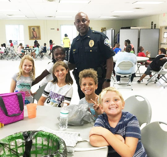 Lt. Steve Bland with the Palm Bay Police Department visits with children eating lunch at Lipscomb Community Center. Aug. 6 is National Night Out. Photo supplied by Palm Bay Police Department