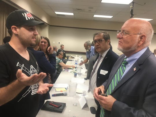 George Elias, left, a volunteer with the Cincinnati nonprofit Caracole, talks with Dr. Robert Redfield, right, director of the U.S. Centers for Disease Control and Prevention, at a statewide conference at Xavier University on how Ohio will deploy new federal dollars to reduce new HIV infections over the next 10 years.