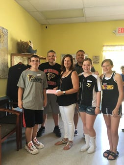 Football player LJ Walther, Board President Tim Bart, board member Brian Rawlins, and cheerleaders Kaitlyn Fleisher, and Kati Hutchins present a donation to Flemington Area Food Pantry Executive Director Jeannine Gorman (center).