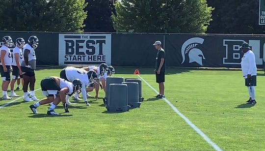 Michigan State's starting defensive line goes through drills as assistant coach Ron Burton (far right) watches during the Spartans' first preseason practice Thursday, Aug. 1, 2019, in East Lansing, Michigan.