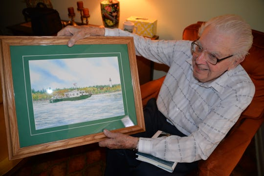 Howard Tanner shows off a painting of the Research Vessel Tanner, which is part of the Michigan Department of Natural Resources' fleet. The boat was named for him in 2016 and focuses on assessments of lake trout and walleye populations and fish community changes in Saginaw Bay and the St. Mary's River.