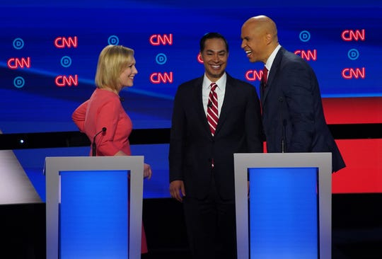 (left to right) Democratic presidential candidate U.S. Sen. Kirsten Gillibrand, Democratic presidential candidate former Housing and Urban Development Secretary Julian Castro and Democratic presidential candidate U.S. Sen. Cory Booker talk during commercial break during the second night of the Democratic presidential debates at the Fox Theatre in Detroit on Wednesday, July 31, 2019.