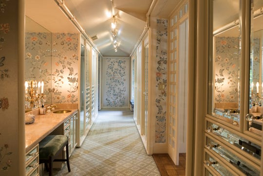 A long hall in the owners' suite is the opulent woman's dressing room. It's lined down both sides with closets and drawers that have fronts of beveled mirror. The luxurious De Gournay wall covering, hand-painted silk, is continued from the bedroom into this room.