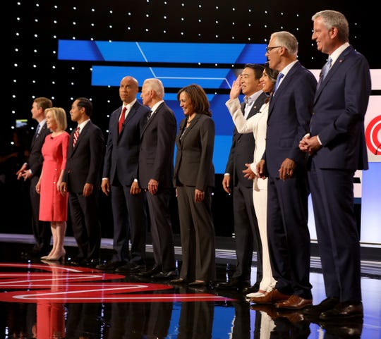 Democratic Presidential candidates line up waving to the crowd before the start of the debate at the Fox Theatre in Detroit, Michigan on Wednesday, July 31, 2019. 