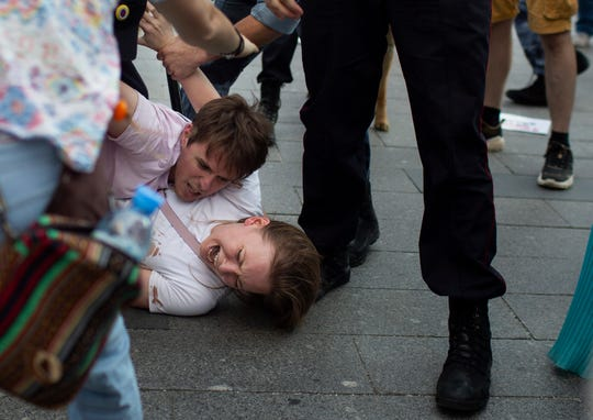 In this photo taken on Saturday, July 27, 2019, Inga Kudracheva screaming as her boyfriend Boris Kantorovich lies atop her while police officers try to detain him during an unsanctioned protest in Moscow. Images of the young couple have been spread on social media. They say the crackdown by police has left them shaken but with their resolve strengthened.