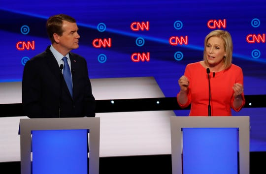 Sen. Michael Bennet, D-Colo., listens as Sen. Kirsten Gillibrand, D-N.Y. speaks during the second of two Democratic presidential primary debates.