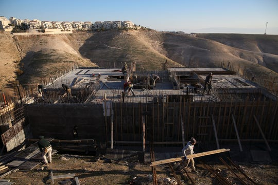 In this Feb. 7, 2017 file photo, Palestinian laborers work at a construction site in the Israeli settlement of Maale Adumim, near Jerusalem. The Israeli Cabinet unanimously approved a proposal to build over 700 housing units for Palestinians in addition to 6,000 Israeli settlement housing units in the West Ban, on Wednesday, July 31, 2019.