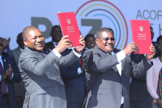 Mozambique President Filipe Nyusi, right, and Renamo leader Ossufo Momade after signing a peace accord at Gorongosa National Park, about 170 kilometres from Beira, Mozambique, Thursday, Aug, 1, 2019.