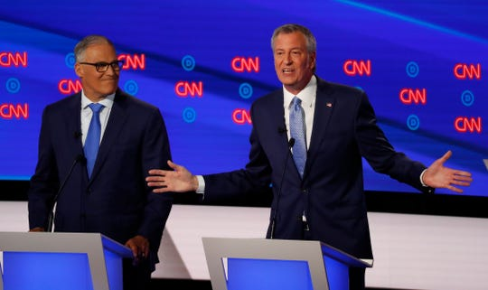 Washington Gov. Jay Inslee listens as New York City Mayor Bill de Blasio speaks during the second of two Democratic presidential primary debates.