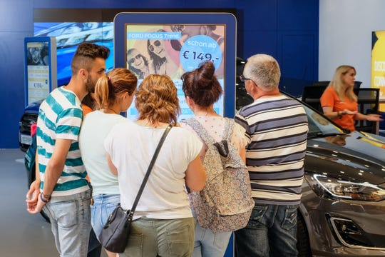 People at a mall in Saarbuken, Germany check out a Ford Motor Co. 'Smart Lab,' a  car display designed to help dealerships generate sales leads in new ways.