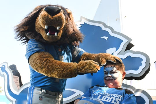 Drew Bradley, 7, has his picture taken with Lions mascot Roary on Thursday.