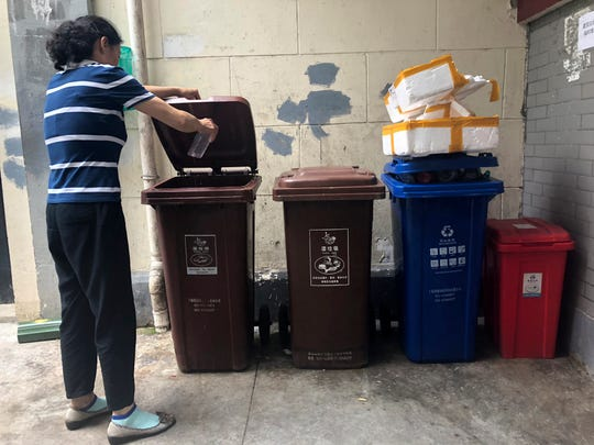 In this  July 22, 2019, photo, a resident pours kitchen wash in a garbage container marked for wet garbage in a residential community in Shanghai. China's biggest city has dived headfirst into a trash sorting program that marks the country's first serious attempt at cutting the amount of garbage headed for landfills nationwide.