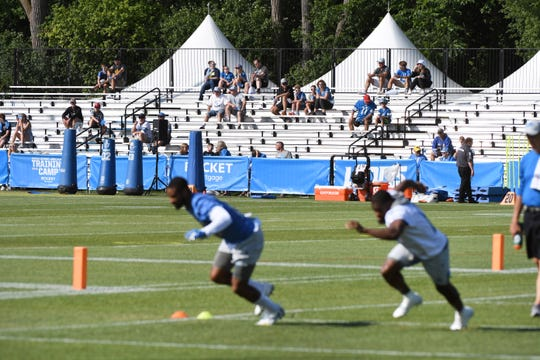 Detroit Lions fans watch as players go through drills during training camp.