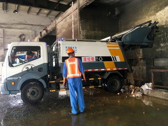 In this July 23, 2019, photo, a trash collection truck deposits its load of wet garbage at a trash station in Shanghai. China's biggest city has dived headfirst into a trash sorting program that marks the country's first serious attempt at cutting the amount of garbage headed for landfills nationwide. (AP Photo/Fu Ting)
