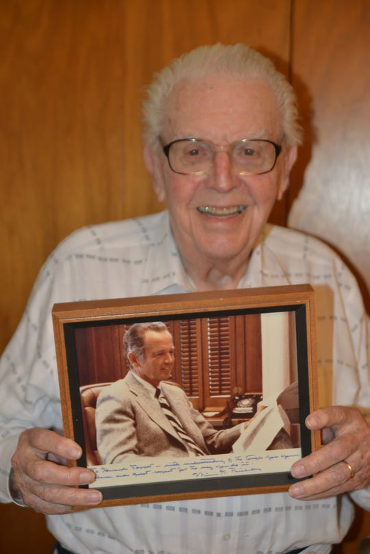 Howard Tanner holds a framed, signed photo from former Michigan Gov. George Milliken, thanking him for his contribution to Michigan conservation. Tanner introduced several species of salmon to state waterways, which helped clean up the Great Lakes in the 1960s.