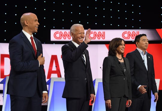 Former Vice President Joe Biden waves to the crowd, flanked by fellow candidates including New Jersey Sen. Cory Booker (left), California Sen. Kamala Harris and New York businessman Andrew Yang on stage before the start of the Democratic presidential debate at the Fox Theatre in Detroit, Michigan on July 31, 2019.