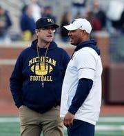 Michigan head coach Jim Harbaugh (left) has turned the offense over to new coordinator Josh Gattis (right).